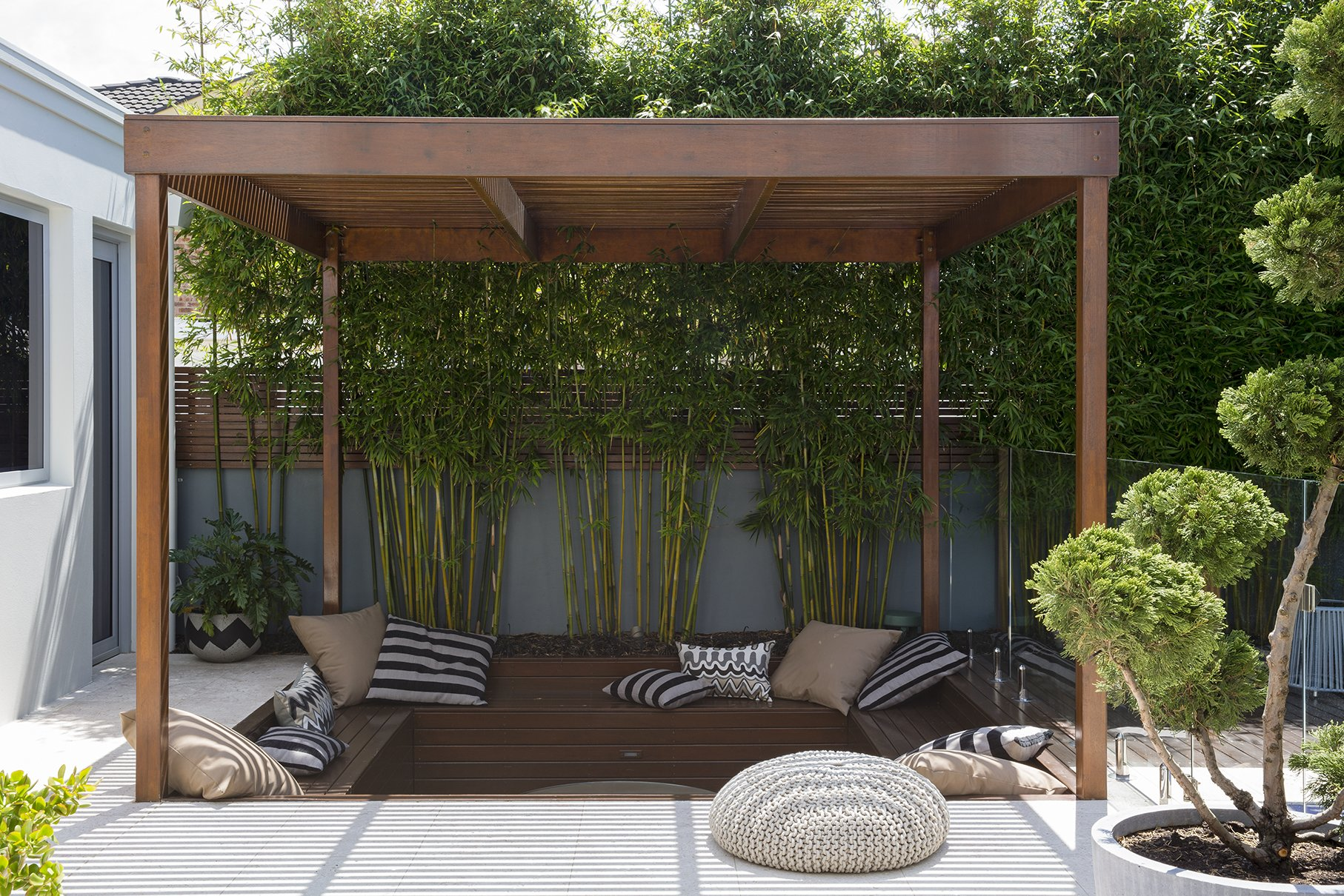 Timber sheltered area with seating and cushions in a backyard