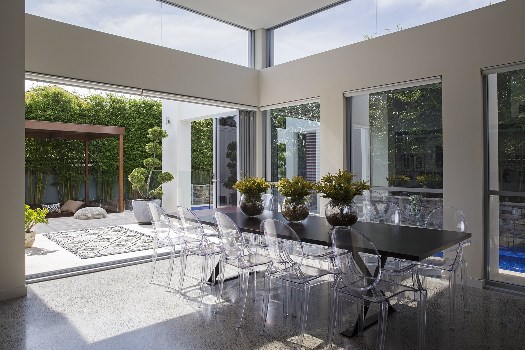 Open living space with a large dining table and clear chairs