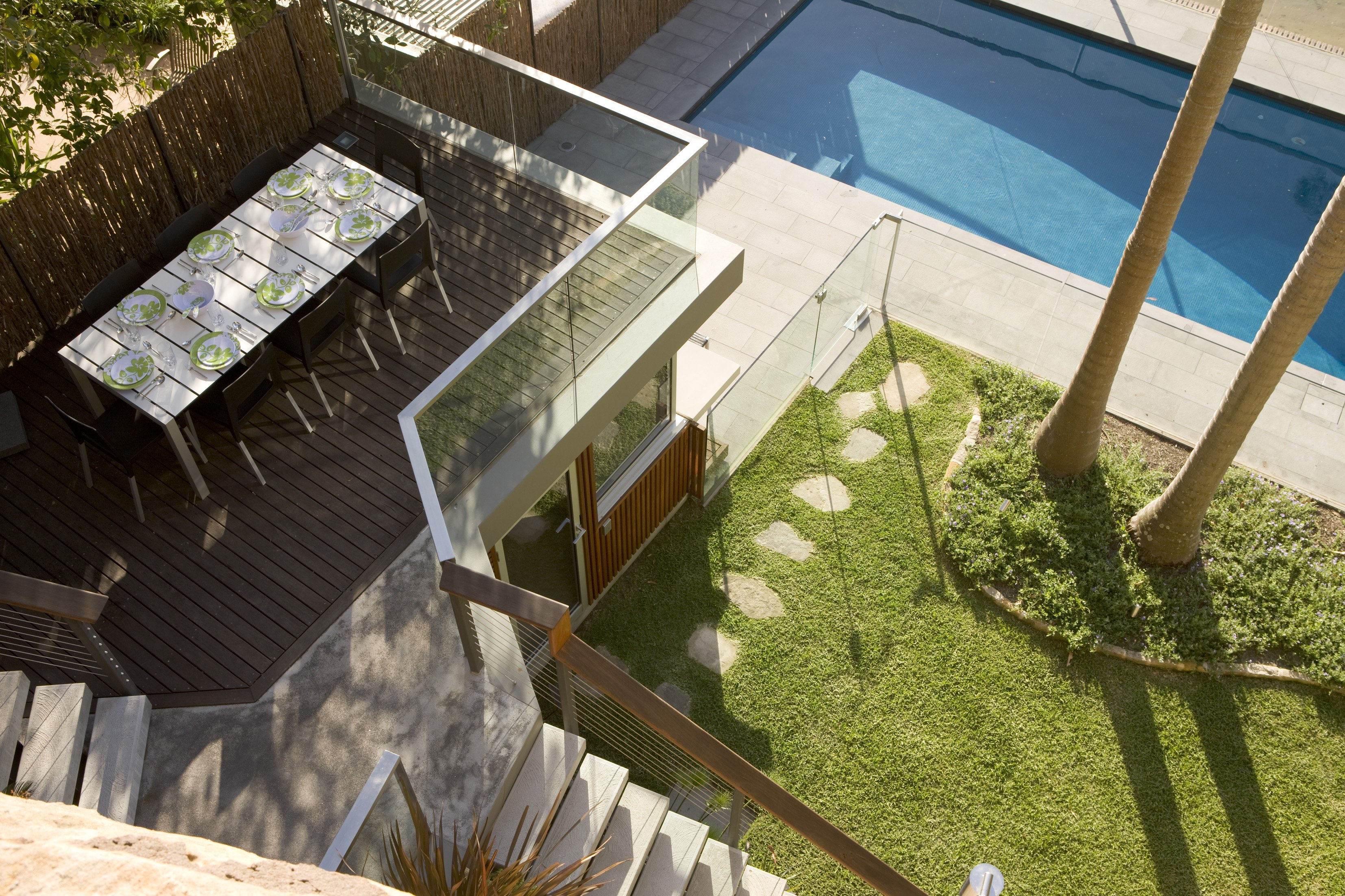 A timber deck with a dining table, onlooking a pool area