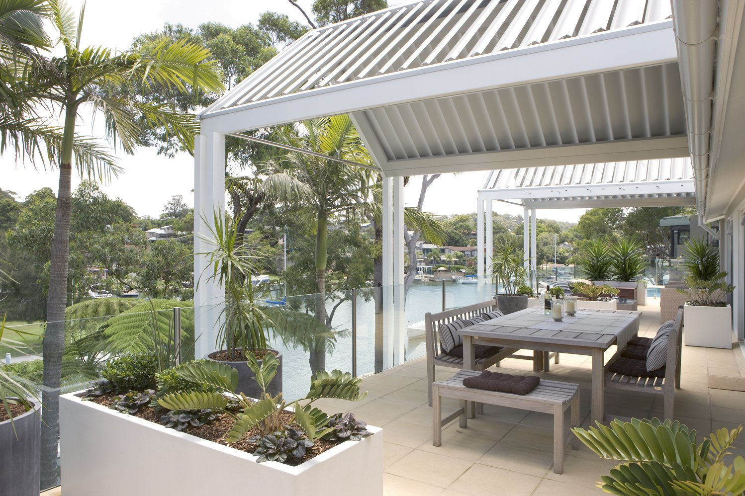 White pergola area with dining table overlooking the water