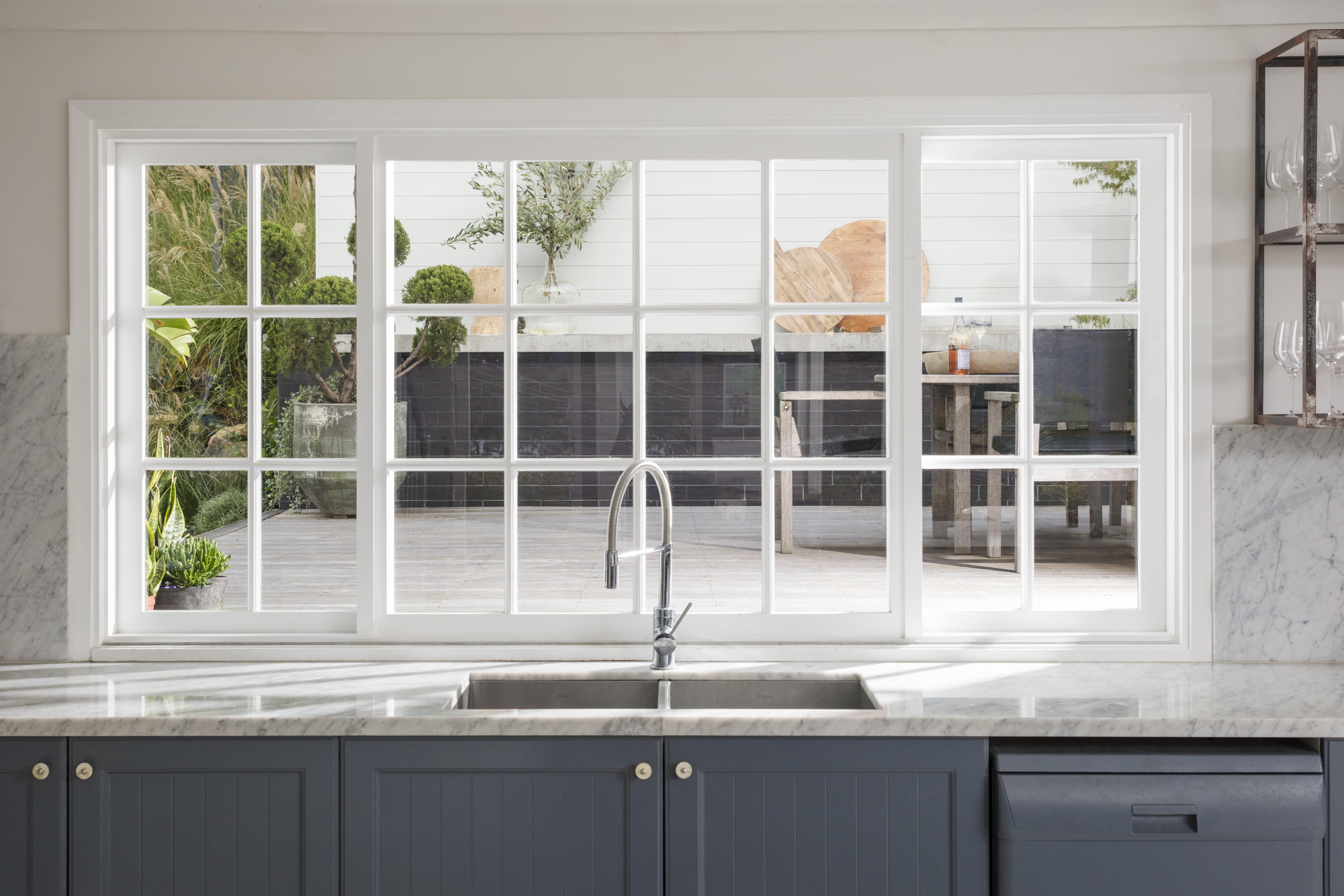 Kitchen basin below white framed windows