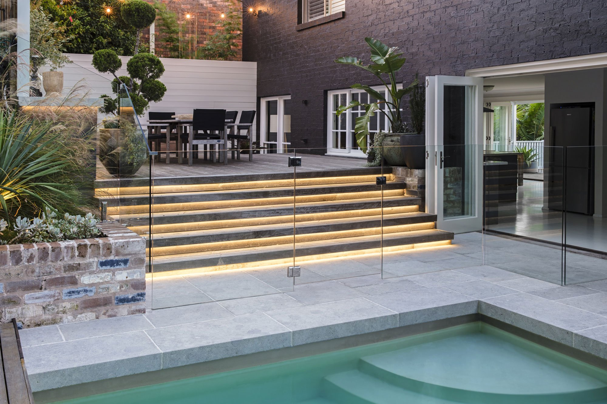 Open garden design with an in-ground pool and seating area
