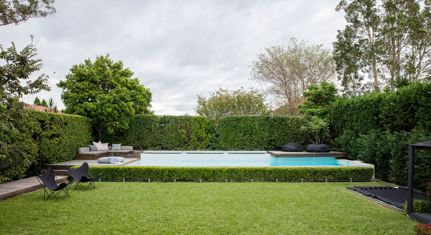 Landscaped lawn an in-ground pool with glass fencing