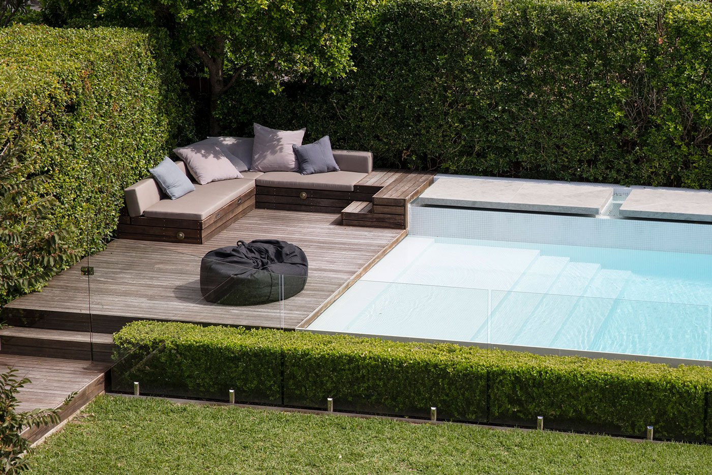 Above ground pool design surrounded by chairs and timber decking
