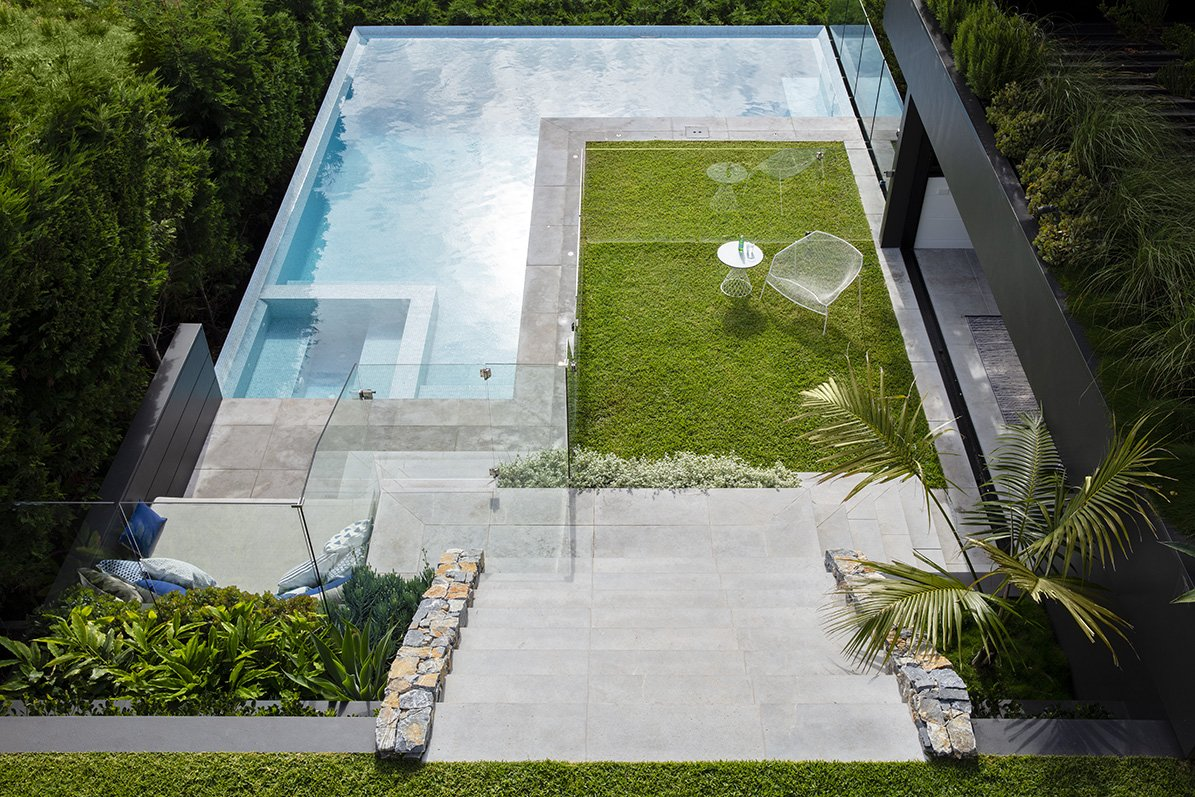 Concrete stairs leading down into a pool design over looking water views