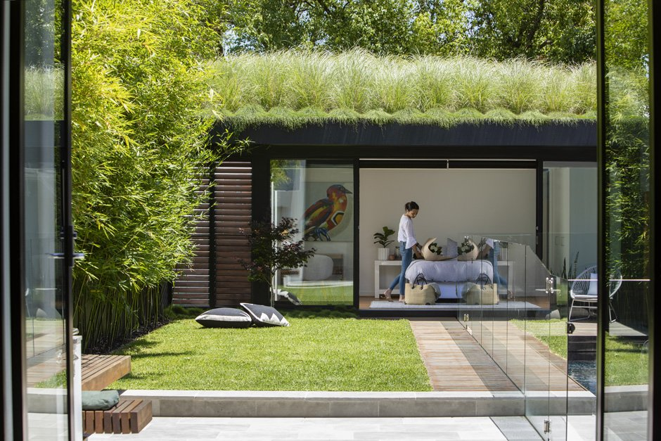 Contemporary garden design with a woman standing in a pool house in a backyard